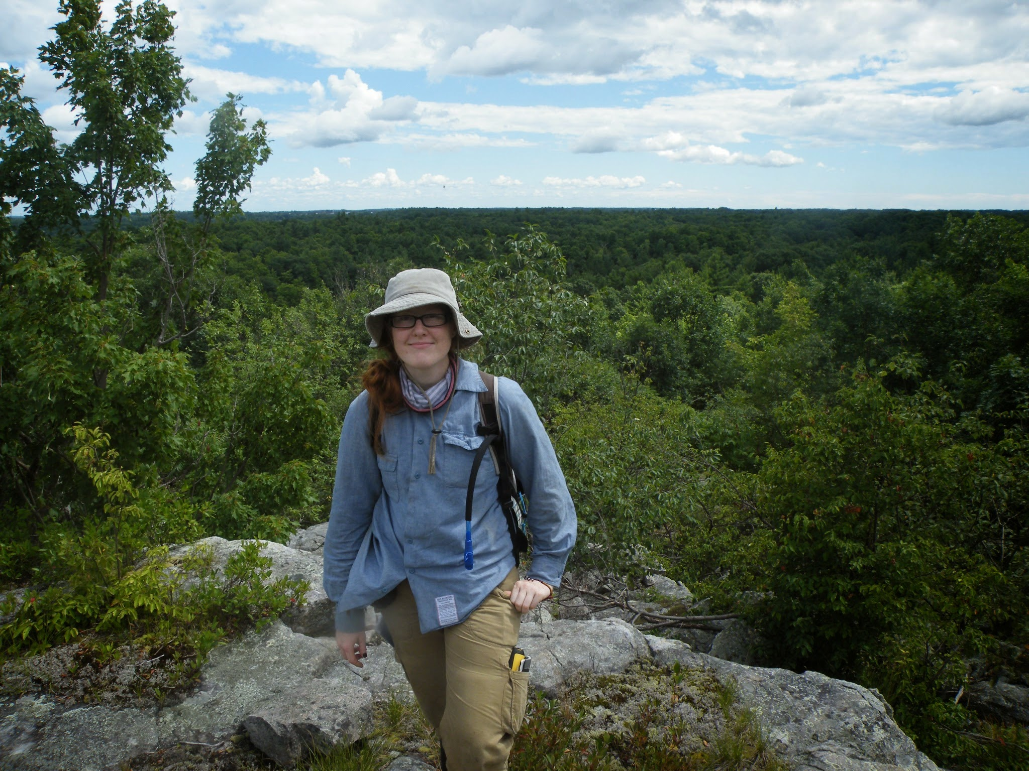 A young woman in field gear stands at a lookout point with a large forested area in the background